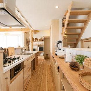 横浜のアジアンスタイルのおしゃれなアイランドキッチン (シングルシンク、フラットパネル扉のキャビネット、中間色木目調キャビネット、白いキッチンパネル、無垢フローリング、茶色い床) の写真