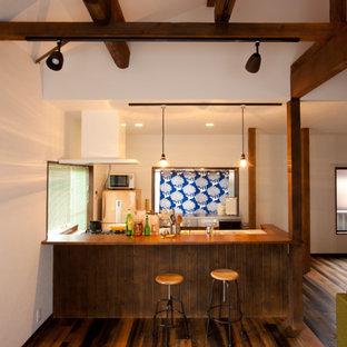 Offene, Zweizeilige Asiatische Küche mit Waschbecken, bunten Elektrogeräten, dunklem Holzboden, Kücheninsel und braunem Boden in Tokio Peripherie