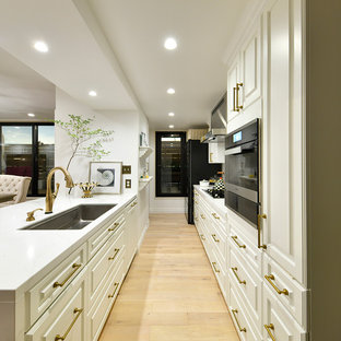 東京23区のトラディショナルスタイルのおしゃれなペニンシュラキッチン (シングルシンク、レイズドパネル扉のキャビネット、白いキャビネット、淡色無垢フローリング、ベージュの床) の写真