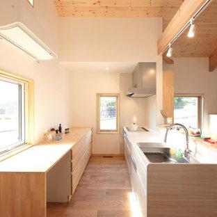 他の地域のカントリー風おしゃれなキッチン (シングルシンク、インセット扉のキャビネット、中間色木目調キャビネット、人工大理石カウンター、淡色無垢フローリング、アイランドなし、茶色い床、白いキッチンカウンター) の写真