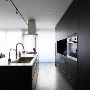 Foto de cocina lineal, moderna, abierta, con fregadero bajoencimera, armarios con paneles lisos, puertas de armario negras, encimera de acero inoxidable, electrodomésticos de acero inoxidable, suelo de cemento y una isla