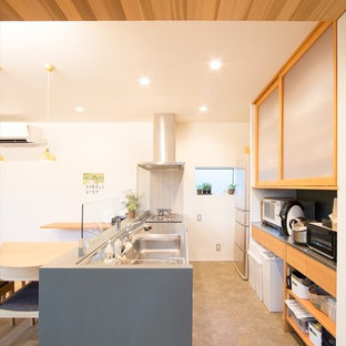 他の地域の小さいモダンスタイルのおしゃれなキッチン (インセット扉のキャビネット、淡色木目調キャビネット、ステンレスカウンター、シングルシンク、グレーの床) の写真