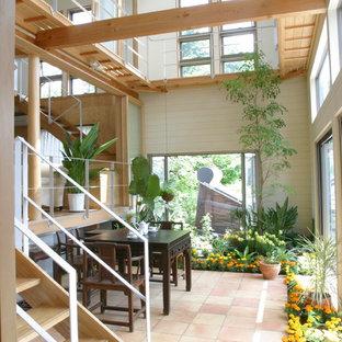 Réalisation d'une véranda champêtre avec un sol en carreau de terre cuite, un plafond standard et un sol orange.