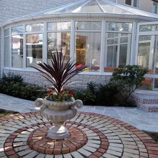 Exemple d'une véranda chic avec un sol en vinyl, un plafond en verre et un sol rose.