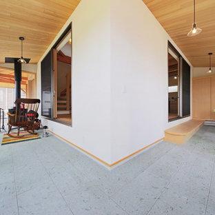 他の地域の和風のおしゃれなサンルーム (薪ストーブ、石材の暖炉まわり、標準型天井、グレーの床) の写真
