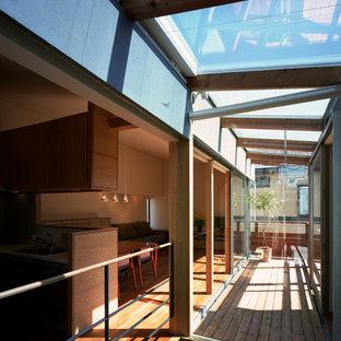 Diseño de galería asiática, de tamaño medio, sin chimenea, con suelo de madera en tonos medios, marco de chimenea de yeso, techo de vidrio y suelo marrón