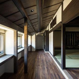 Idée de décoration pour une grand véranda tradition avec un sol en bois foncé et un sol marron.