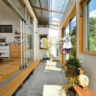 Immagine di una veranda nordica con pavimento in cemento, soffitto in vetro e pavimento grigio