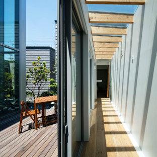 Modern inredning av ett uterum, med plywoodgolv, glastak och brunt golv