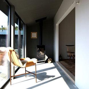 他の地域のラスティックスタイルのおしゃれなサンルーム (コンクリートの床、薪ストーブ、標準型天井、グレーの床) の写真