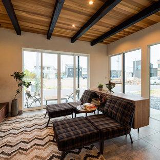 他の地域の中くらいのインダストリアルスタイルのおしゃれなオープンシアタールーム (白い壁、セラミックタイルの床、壁掛け型テレビ、グレーの床) の写真