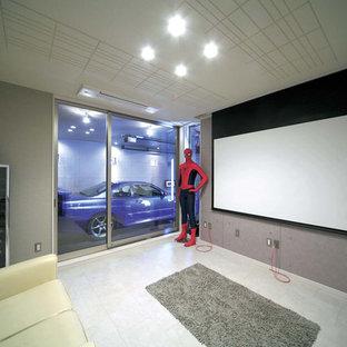 他の地域のインダストリアルスタイルのおしゃれな独立型シアタールーム (グレーの壁、プロジェクタースクリーン、グレーの床) の写真