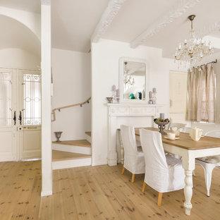 他の地域のトラディショナルスタイルのおしゃれなダイニング (淡色無垢フローリング、白い壁、標準型暖炉、ベージュの床) の写真