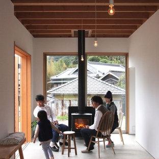 Ejemplo de comedor de cocina escandinavo, pequeño, con paredes blancas, suelo de madera en tonos medios, estufa de leña, marco de chimenea de hormigón y suelo marrón