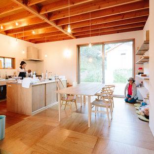 Modelo de comedor de cocina nórdico, pequeño, con paredes blancas, suelo de madera en tonos medios, estufa de leña, marco de chimenea de hormigón y suelo marrón
