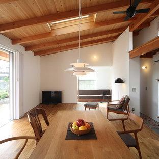 他の地域のおしゃれなLDK (白い壁、無垢フローリング、薪ストーブ、漆喰の暖炉まわり、茶色い床) の写真