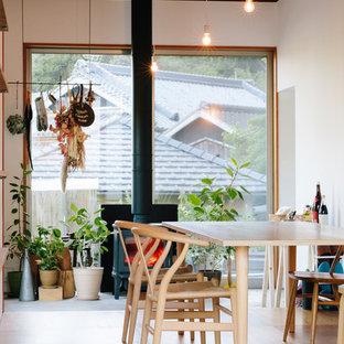他の地域の小さいアジアンスタイルのおしゃれなダイニングキッチン (白い壁、無垢フローリング、薪ストーブ、コンクリートの暖炉まわり、茶色い床) の写真