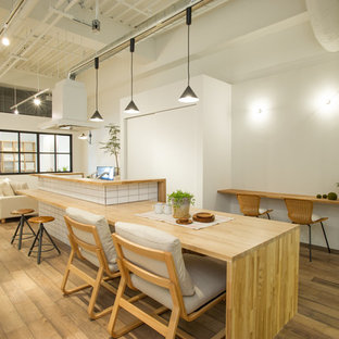 Example of an urban medium tone wood floor and brown floor great room design in Tokyo with white walls