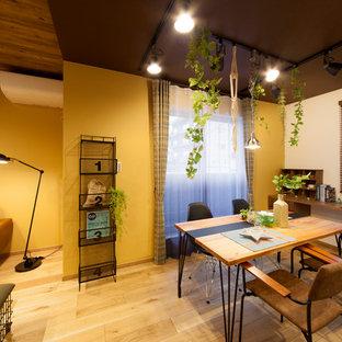 Esempio di una piccola sala da pranzo aperta verso il soggiorno industriale con pareti gialle, pavimento in legno massello medio e pavimento marrone
