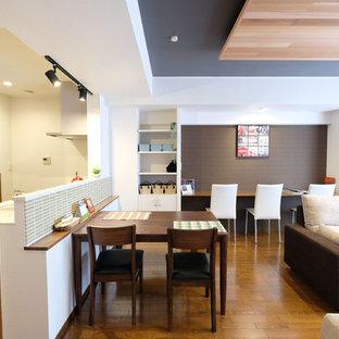 Ispirazione per una grande sala da pranzo aperta verso il soggiorno minimalista con pareti marroni, pavimento in compensato, nessun camino e pavimento marrone