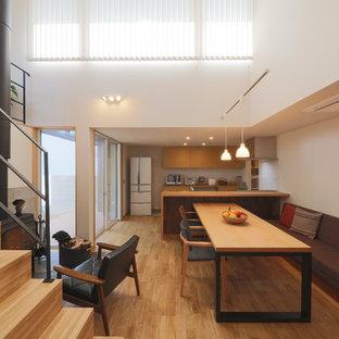 Imagen de comedor de cocina nórdico con paredes blancas, suelo de madera en tonos medios, estufa de leña, marco de chimenea de hormigón y suelo marrón