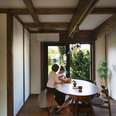 Example of a dark wood floor and brown floor dining room design in Other with white walls