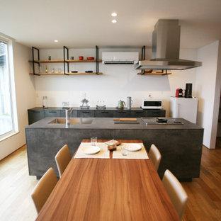 Foto di una sala da pranzo aperta verso la cucina minimalista con pareti bianche, pavimento in legno massello medio, soffitto in carta da parati e carta da parati