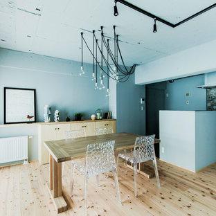 Idee per una sala da pranzo aperta verso il soggiorno industriale con pareti blu, pavimento in legno massello medio e pavimento marrone