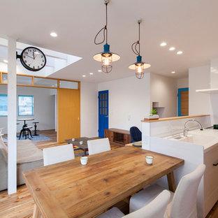 Idee per una sala da pranzo aperta verso il soggiorno etnica con pareti bianche, pavimento in legno massello medio e pavimento marrone