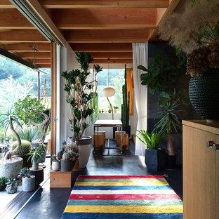 Foto di una piccola sala da pranzo boho chic con nessun camino, pareti bianche e pavimento nero