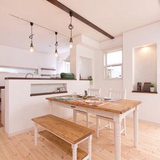 Imagen de comedor campestre, abierto, sin chimenea, con paredes blancas, suelo de madera en tonos medios y suelo beige