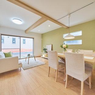 Aménagement d'une salle à manger ouverte sur le salon scandinave avec un mur vert, un sol en contreplaqué et un sol beige.