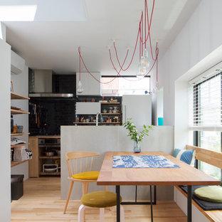 Cette photo montre une salle à manger ouverte sur la cuisine tendance avec un sol en bois clair, un sol turquoise et un mur blanc.