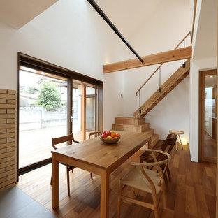 他の地域のミッドセンチュリースタイルのおしゃれなLDK (白い壁、濃色無垢フローリング、薪ストーブ、レンガの暖炉まわり、茶色い床) の写真