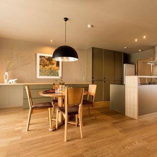 Idée de décoration pour une salle à manger ouverte sur la cuisine minimaliste avec un mur beige et un sol en contreplaqué.