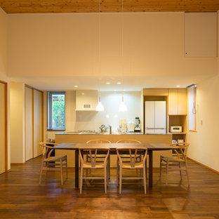 他の地域の中サイズのアジアンスタイルのおしゃれなLDK (白い壁、濃色無垢フローリング、薪ストーブ、漆喰の暖炉まわり、茶色い床) の写真