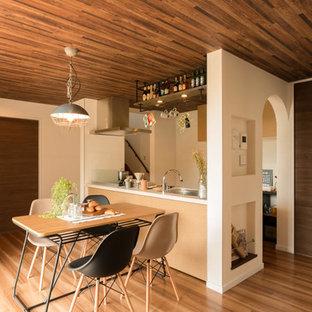 Asiatische Wohnküche mit weißer Wandfarbe und braunem Holzboden in Sonstige