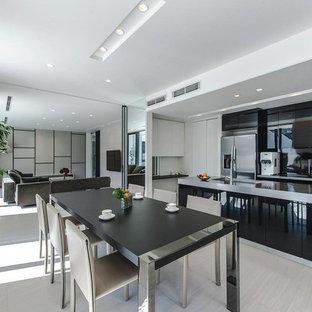 コンテンポラリースタイルのおしゃれなLDK (ベージュの床、フラットパネル扉のキャビネット、黒いキャビネット、黒いキッチンパネル、シルバーの調理設備の) の写真