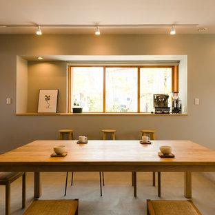 他の地域の中サイズのコンテンポラリースタイルのおしゃれなダイニングキッチン (グレーの壁、コンクリートの床、暖炉なし、グレーの床) の写真