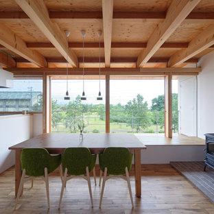 京都のアジアンスタイルのおしゃれなダイニングキッチン (白い壁、無垢フローリング、薪ストーブ、タイルの暖炉まわり、茶色い床) の写真
