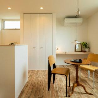 На фото: маленькая гостиная-столовая в стиле рустика с белыми стенами, паркетным полом среднего тона, коричневым полом, потолком с обоями и обоями на стенах без камина с