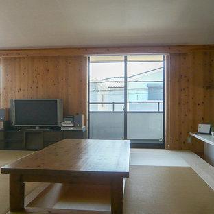 Immagine di una sala da pranzo aperta verso il soggiorno country di medie dimensioni con pareti marroni, pavimento in tatami, nessun camino e pavimento verde