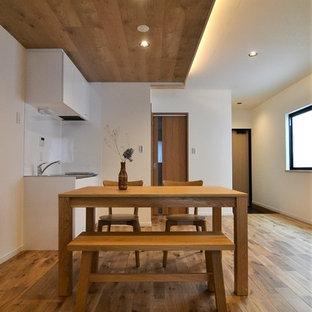 Foto di una sala da pranzo etnica con pareti bianche, pavimento in legno massello medio e pavimento marrone