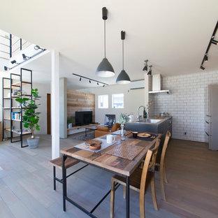 Diseño de comedor urbano, abierto, con paredes blancas, suelo de madera pintada y suelo gris