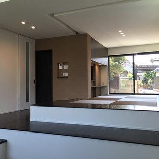 Foto di una sala da pranzo aperta verso il soggiorno moderna di medie dimensioni con pareti bianche, pavimento marrone, pavimento in tatami e nessun camino