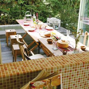 Immagine di una sala da pranzo aperta verso il soggiorno tropicale con pareti bianche, pavimento in compensato e pavimento marrone