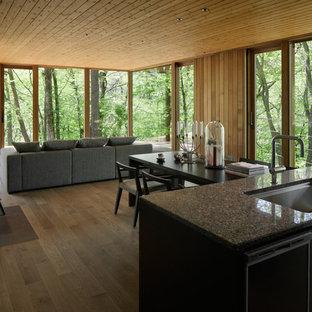Esempio di una sala da pranzo aperta verso il soggiorno design con pareti marroni, pavimento in legno verniciato, stufa a legna e pavimento grigio