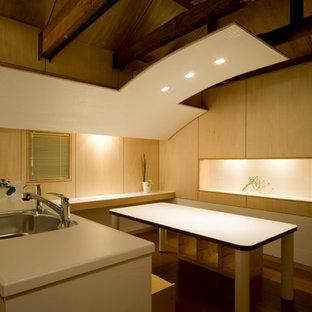 Ispirazione per una piccola sala da pranzo aperta verso il soggiorno moderna con pareti beige, pavimento in compensato, pavimento marrone, travi a vista e pareti in legno
