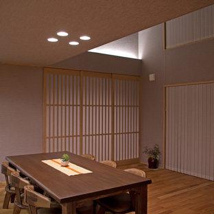 Esempio di una sala da pranzo etnica con pareti grigie, pavimento in legno massello medio e pavimento marrone