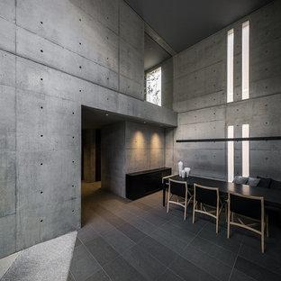 Exemple d'une grand salle à manger industrielle avec un mur gris et un sol gris.